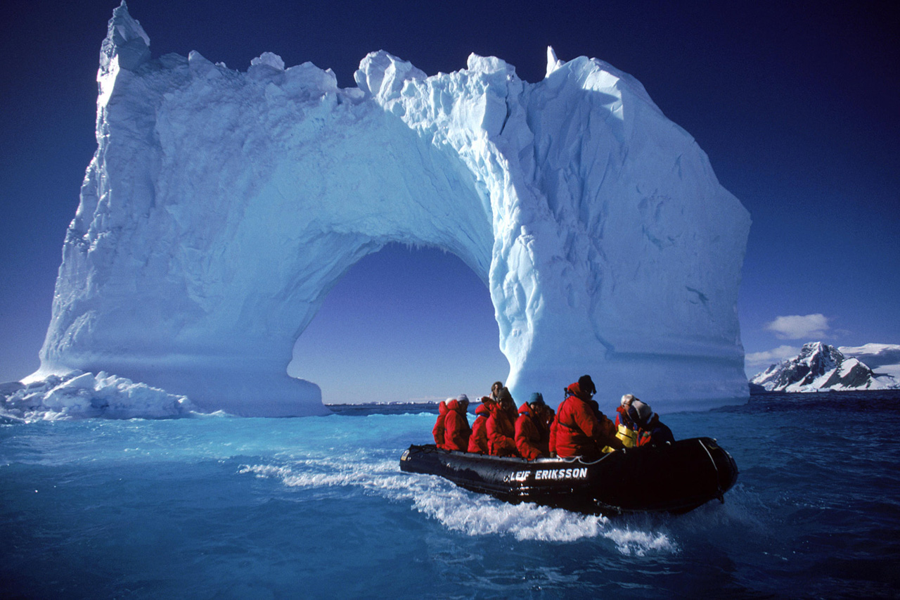Boating by an iceberg arch near Yalour Islands, Antarctica.